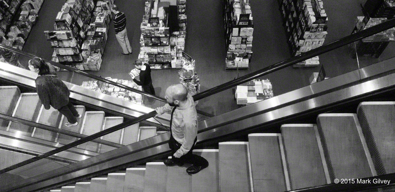 Black and white photo of customers going up and down an escalator in a book store.